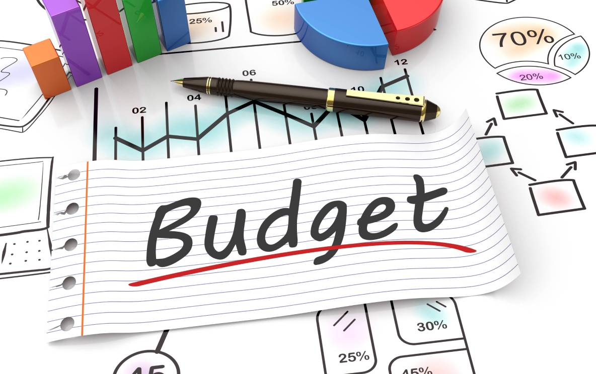 "The word ""budget"" is written on a piece of paper, lying on a desk amidst calculations, graphs, and expense projections."
