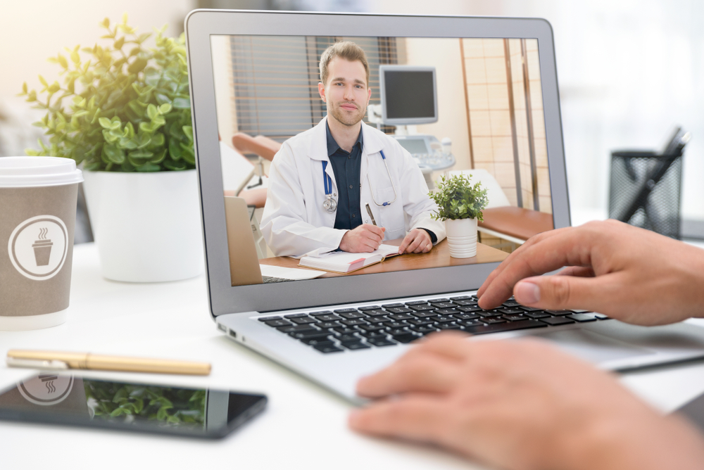 A patient connects online with a male physician to get a checkup via telemedicine services.