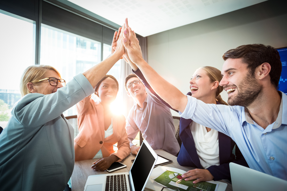 Members of sales and marketing teams gather around a conference table and give high fives in support of their shared business goals.
