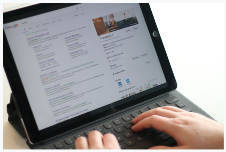 Someone's hands type at a keyboard while a tablet screen displays a Google search result page.