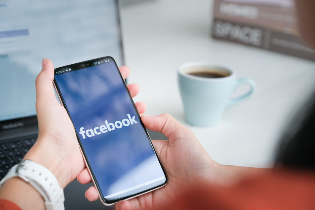 """Person holding their smartphone with their facebook app loading up as the phone displays """"Facebook"""" on its screen."""