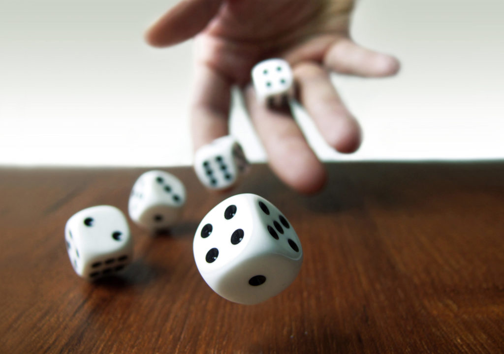 Hand rolling two dice on a wooden desk against a white background.