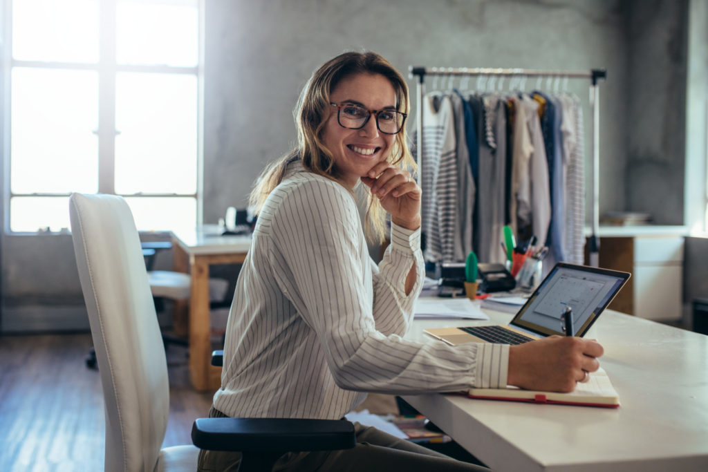 Small business owner works at her laptop in her studio with a clothes rack in the background.