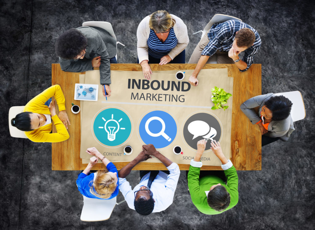 Top view of diverse employees around a conference table with graphics for inbound marketing.