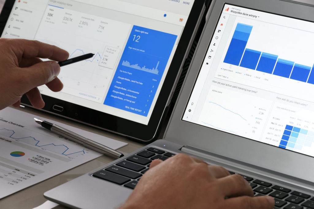 Business man points to google analytics website charts on his side-by-side laptops.